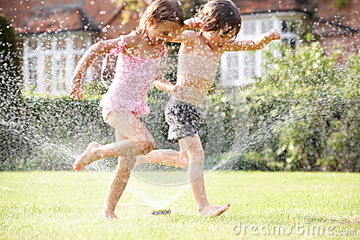 two-children-running-garden-sprinkler-26103135